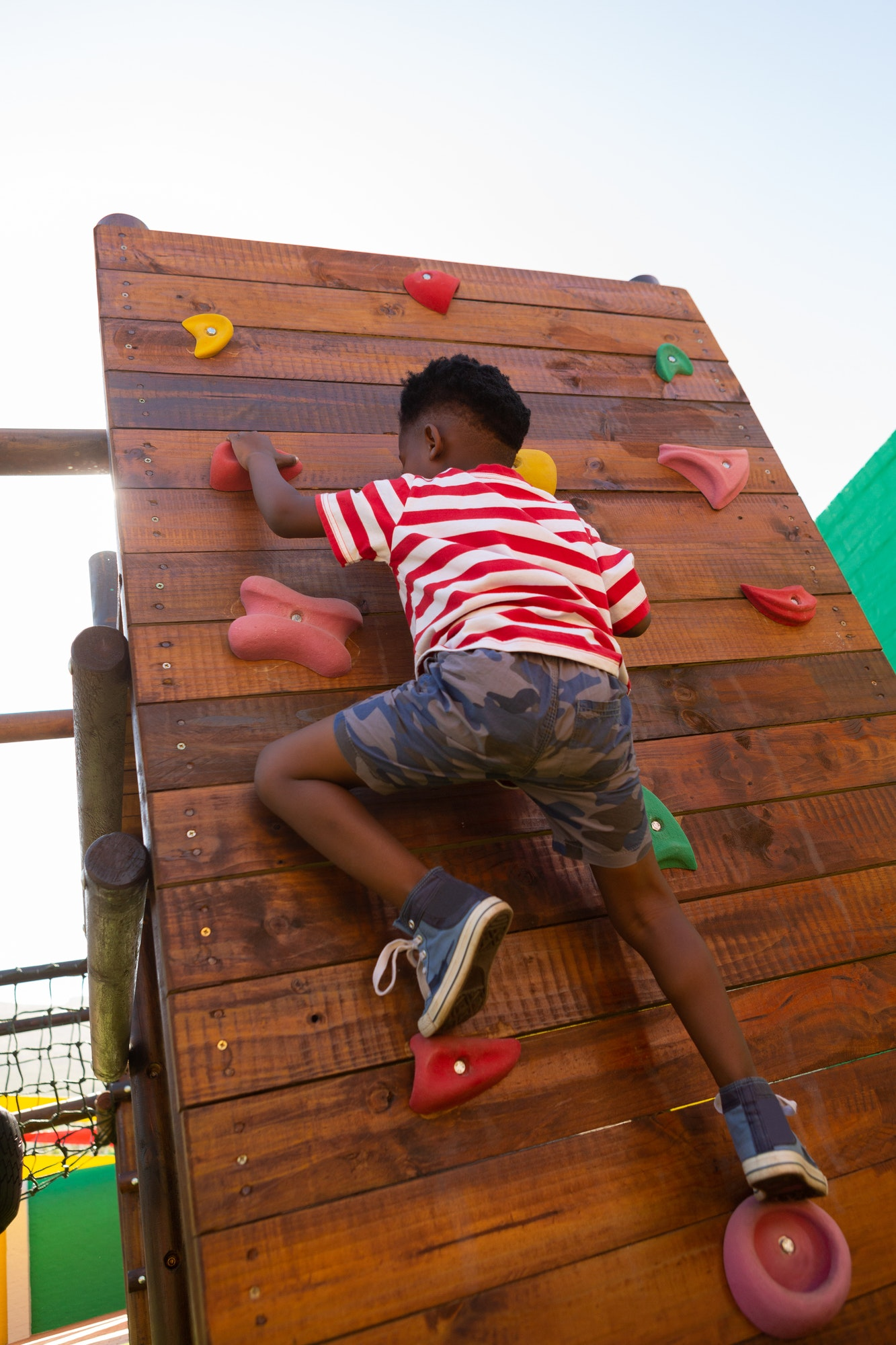 Cute schoolboy climbing a wall in the school playground on a sunny day